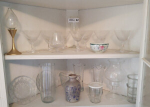 Contents of 2 Middle Shelves in Corner Cabinet Including Stemmed Glasses, Glass Serving Platter, Small Pitcher