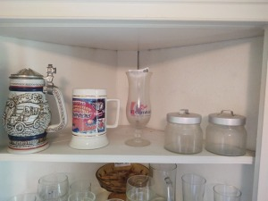 Contents of Upper Shelf in Corner Cabinet Including Collectible Mugs