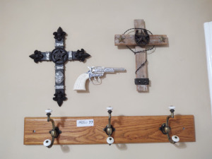 2 western themed decorative crosses, toy western gun, wooden shelf with 3 hooks