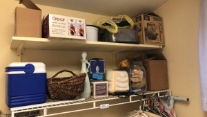 Contents of laundry room corner; ironing board, dusters, laundry baskets, small cooler, etc.
