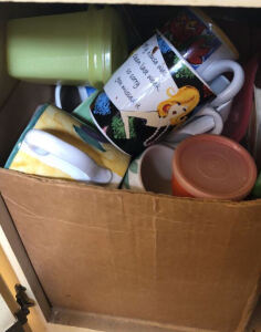 Contents of cabinet; mugs, plastic ware, etc.