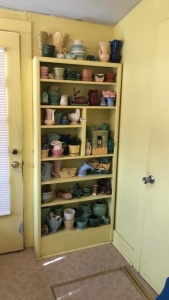 Contents of shelf:  Pottery (several pieces of McCoy, USA)